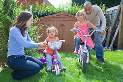 Little girls playing on bikes in the garden with their parents,