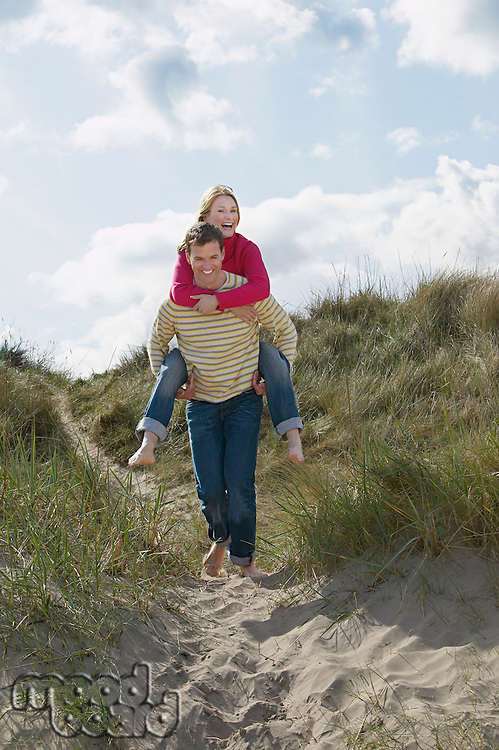 Man giving woman piggy back on sand dunes