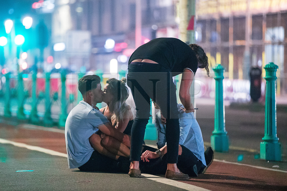 © Licensed to London News Pictures . 26/09/2017. Brighton, UK. A couple kiss as a group sit together on the pavement on Brighton Promenade . Revellers at the end of a night out during Freshers week , when university students traditionally enjoy the bars and clubs during their first nights out in a new city . Photo credit: Joel Goodman/LNP