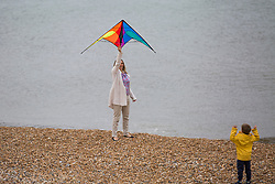 © Licensed to London News Pictures. 07/05/2017. Brighton, UK. A woman and child play with a colourful kite on the beach in Brighton and Hove as low temperatures and grey clouds are hitting the seaside resort. Photo credit: Hugo Michiels/LNP
