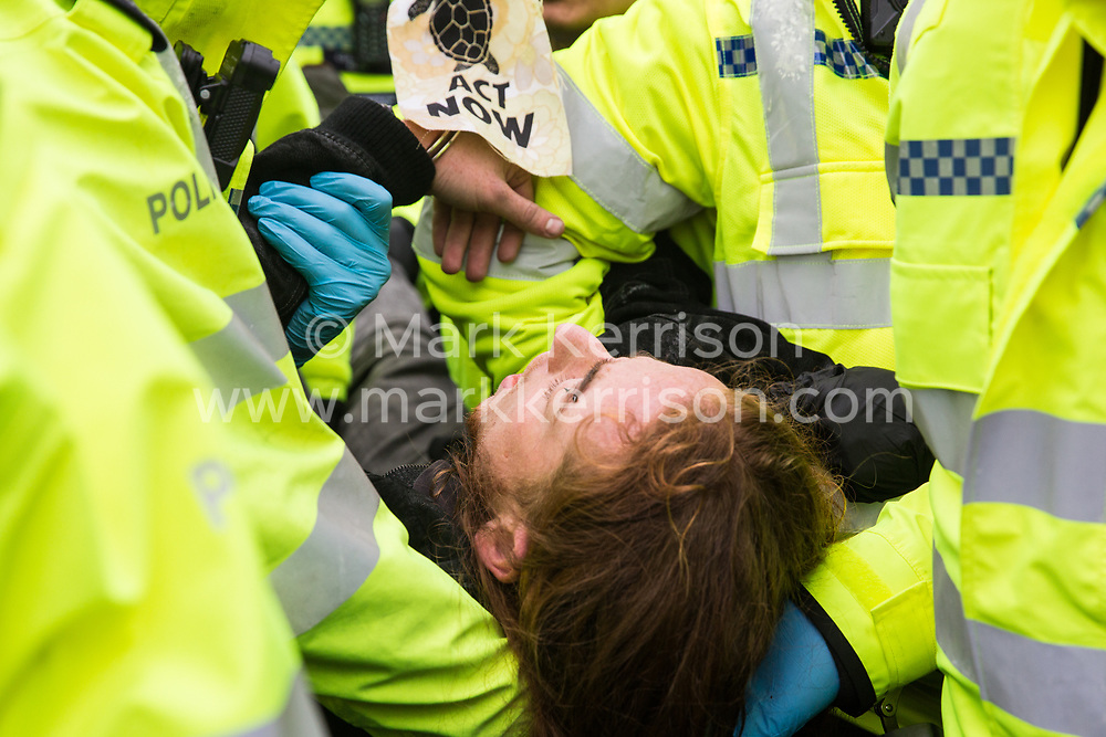 London, UK. 7 October, 2019. A climate activist from Extinction Rebellion holds up a banner reading 'Act Now' as he is arrested by Metropolitan Police officers after glueing himself to a scaffold tower used to block Trafalgar Square on the first day of International Rebellion protests to demand a government declaration of a climate and ecological emergency, a commitment to halting biodiversity loss and net zero carbon emissions by 2025 and for the government to create and be led by the decisions of a Citizens' Assembly on climate and ecological justice.