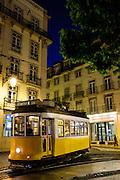 Tram 28 in Lisbon's Chiado neighborhood at dusk.