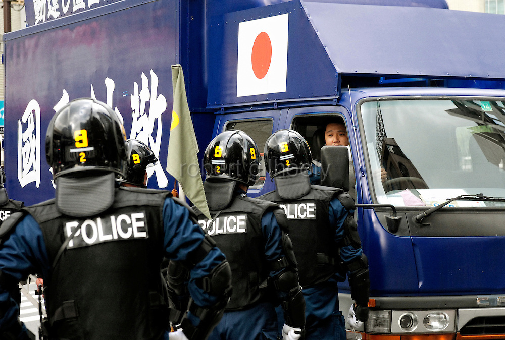 Riot police form a road block to prevent nationalist groups in vans from entering the plush Ginza shopping district of Tokyo, Japan.