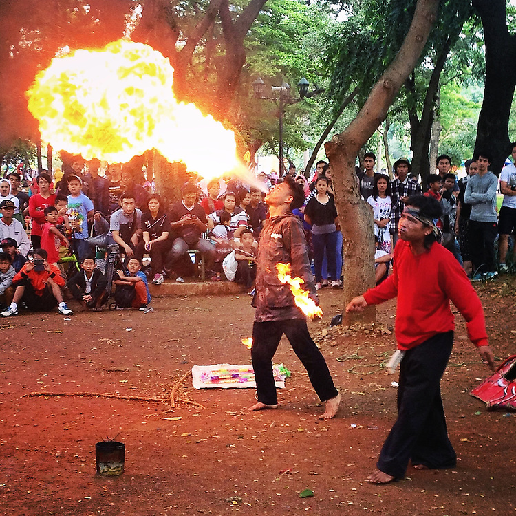 Spectators gather under the cool shade at Monas Square to watch street performers spit fire and extinguish flame with their tongue.