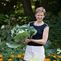 A young twenty-something woman stands in a garden holding a large head of cabbage. She has short blond hair, very fair skin, blue tee shirt and whiteshorts.