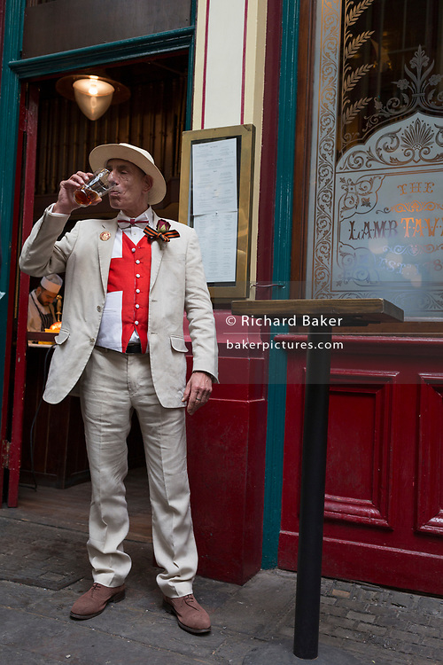 Lunchtime drinker enjoys a pint at a pub in Leadenhall Market in the capital's financial district (aka The Square Mile), on 23rd April, City of London, England.