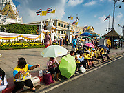 03 DECEMBER 2015 - BANGKOK, THAILAND: People sit on the sidewalk and wait for the annual Trooping of the Colors parade to Sanam Luang to start in Bangkok. The Thai Royal Guards Parade, also known as Trooping of the Colors, occurs every December before the celebration of the birthday of Bhumibol Adulyadej, the King of Thailand. The Royal Guards of the Royal Thai Armed Forces perform a military parade and pledge loyalty to the monarch. Historically, the venue has been the Royal Plaza in front of the Dusit Palace and the Ananta Samakhom Throne Hall. This year it was held on Sanam Luang in front of the Grand Palace.    PHOTO BY JACK KURTZ