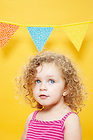 Portrait of blonde hair blue eyed little girl against yellow seamless. Photographed at Photoville Photo Booth September 20, 2015