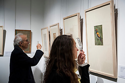 © Licensed to London News Pictures. 02/10/2015. London, UK. Visitors use a magnifying glass to view paintings from the Sven Gahlin Collection of 157 finely painted Indian miniature paintings at the preview of Indian and Islamic Art Week at Sotheby's which runs from 2 to 7 October.   Photo credit : Stephen Chung/LNP