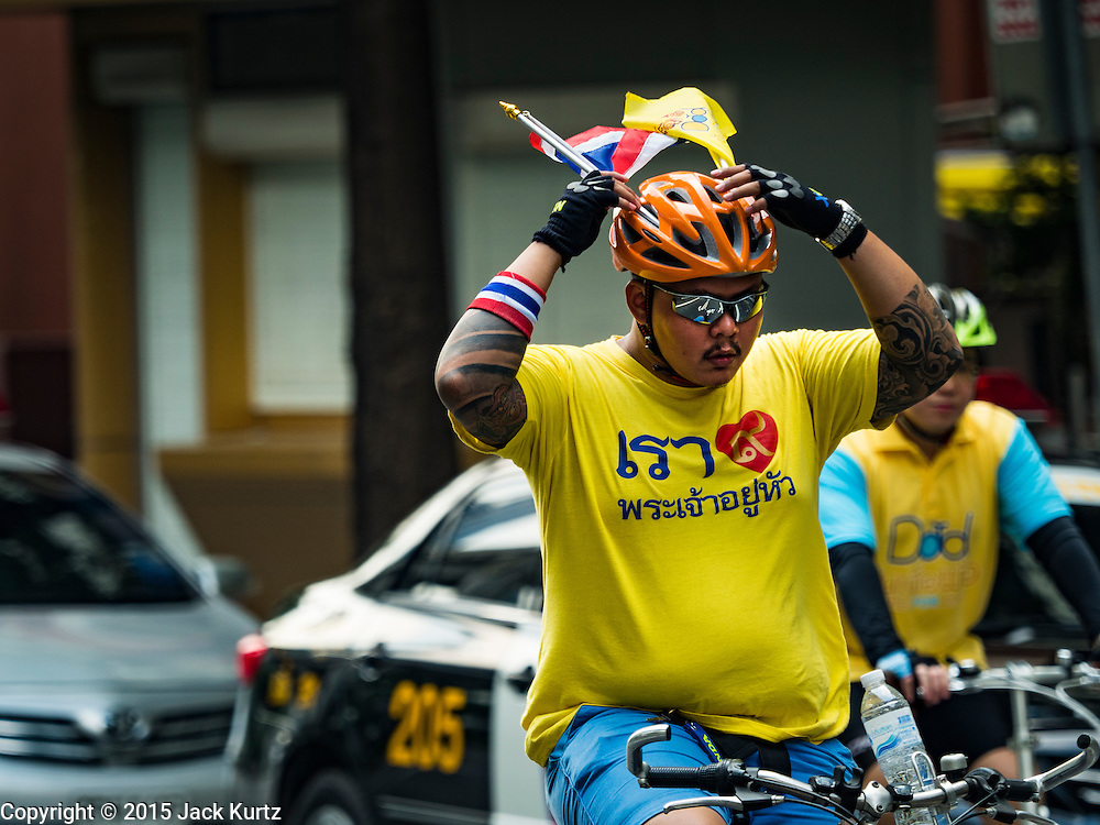 11 DECEMBER 2015 - BANGKOK, THAILAND: A man adjusts his helmet during Bike for Dad in Bangkok. More than 527,000 people registered for the Bike for Dad event to honor Bhumibol Adulyadej, the King of Thailand, whose birthday is also celebrated as Father's Day in Thailand. In Bangkok, 99,999 people registered for Bike for Dad. More than 418,000 people registered for Bike for Dad rides in the provinces outside Bangkok and 9,805 participated in Bike for Dad events outside of Thailand. His Royal Highness Crown Prince Maha Vajiralongkorn, the heir apparent to the Thai crown, led the bike ride in Bangkok. The Bangkok route was 29 kilometers long (18 miles) and traveled through Bangkok and across the Chao Phraya River into Thonburi. Bike for Dad events were held across Thailand.     PHOTO BY JACK KURTZ