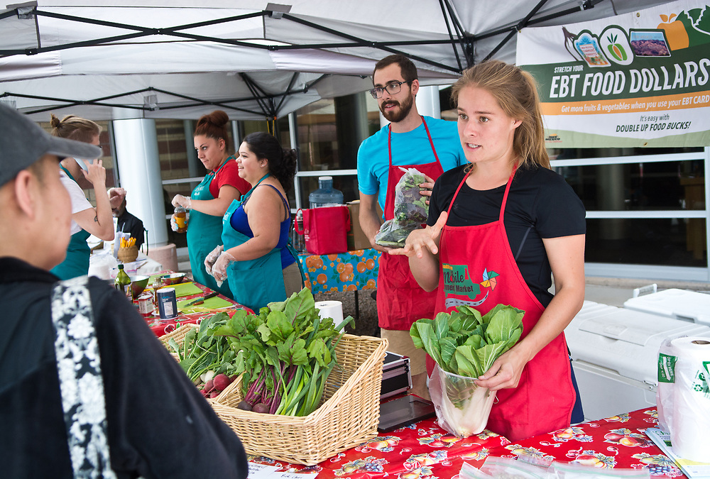 mkb060617f/metro/Marla Brose --  Natalie Donnelly, front right, community food projects coordinator with Presbyteriean Center for Community Health talks to Melissa Lucero about bok choy and some of the other produce for sale at the Mobile Farmers' Market, Tuesday, June 6, 2017. The market made three stops, including one outside of First Choice Community Healthcare at 2001 El Centro Familiar Blvd. SW.  (Marla Brose/Albuquerque Journal)