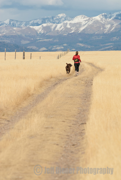 A young woman and her dog run along a country road in northwest Wyoming.