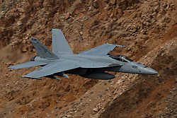 Boeing F/A-18E Super Hornet from United States Navy squadron VFA-25 Fist of the Fleet (AG 402) flies low level through the Jedi Transition, Star Wars Canyon, Death Valley National Park, California, United States of America