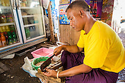 30 APRIL 2013 - MAHACHAI, SAMUT SAKHON, THAILAND:  The owner of a Burmese tea house in Mahachai, Samut Sakhon province, Thailand, cuts vegetables. The Thai fishing industry is heavily reliant on Burmese and Cambodian migrants. Burmese migrants crew many of the fishing boats that sail out of Samut Sakhon and staff many of the fish processing plants in Samut Sakhon, about 45 miles south of Bangkok. Migrants pay as much $700 (US) each to be smuggled from the Burmese border to Samut Sakhon for jobs that pay less than $5.00 (US) per day. There have also been reports that some Burmese workers are abused and held in slavery like conditions in the Thai fishing industry.          PHOTO BY JACK KURTZ