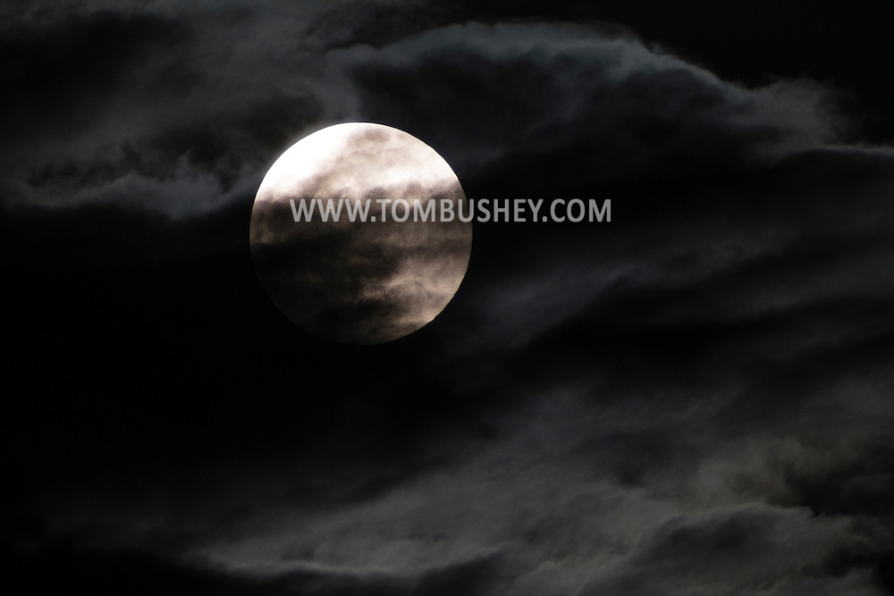 The full moon shines through clouds on May 3, 2015.