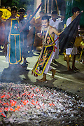 01 OCTOBER 2014 - BANGKOK, THAILAND:  A firewalker looks at the fire pit before the fire walking at Wat Yannawa (also spelled Yan Nawa) during the Vegetarian Festival in Bangkok. The Vegetarian Festival is celebrated throughout Thailand. It is the Thai version of the The Nine Emperor Gods Festival, a nine-day Taoist celebration beginning on the eve of 9th lunar month of the Chinese calendar. During a period of nine days, those who are participating in the festival dress all in white and abstain from eating meat, poultry, seafood, and dairy products. Vendors and proprietors of restaurants indicate that vegetarian food is for sale by putting a yellow flag out with Thai characters for meatless written on it in red.    PHOTO BY JACK KURTZ