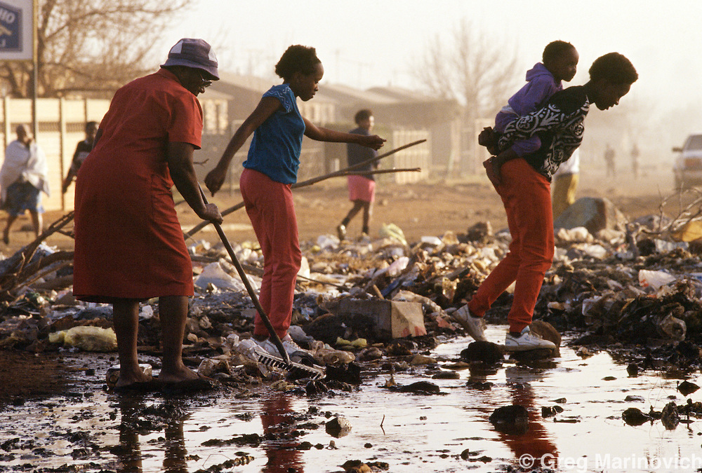 Women and children cross through a river of sewerage flooding a street in Sebokeng, Vaal, South Africa, 1995.