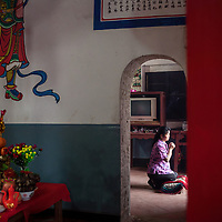 A villager prays to the goddess Mazu at the Wenxing temple.  <br />