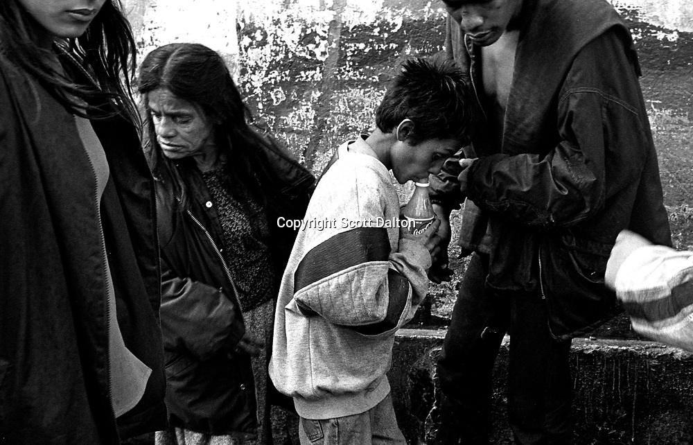 A young boy sniffs glue in Cartucho, a barrio of street people and drug addicts in downtown in Bogotá. (Photo/Scott Dalton)