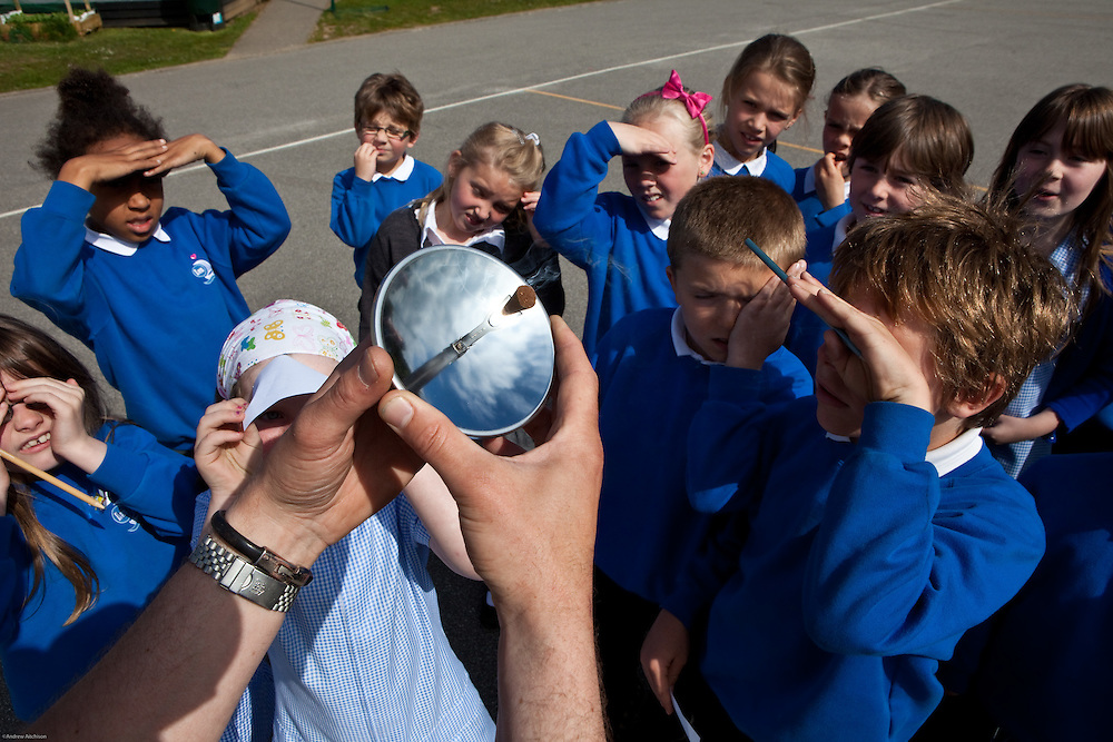Children from year 3 watch a Sundance solar spark lighter in action in the school playground. The device is designed to focus the sun's radiant energy to a point that can reach 1000 degrees. St. Columb Minor school, Cornwall.