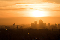 © Licensed to London News Pictures. 28/01/2015. London, UK. Warm orange sunrise over the City of London seen from Hampstead Heath during cold weather this morning. Photo credit : Vickie Flores/LNP