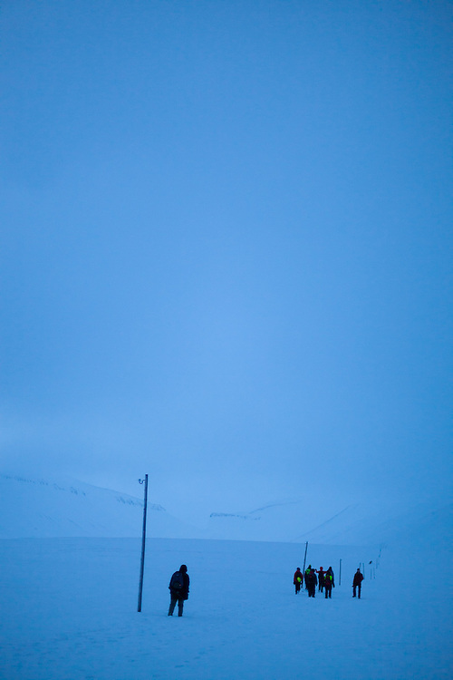 UNIS students from nearby Longyearbyen hike across Sverdruphamaren, Svalbard, past abandoned utility poles.