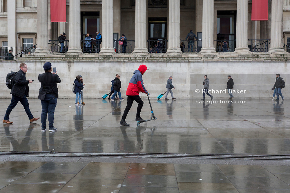 A young man scoots beneath the columned architecture of the National Gallery in Trafalgar Square, Westminster, on 9th April 2019, in London, England.
