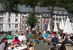 Busy restaurant in Marrktplatz in historic village of Monschau in Germany