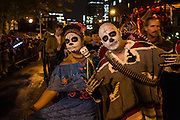 New York, NY, October 31, 2013. A couple in Mexican-themed costumes, with faces painted as catrinas, in New York's Greenwich Village Halloween Parade.
