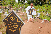 "27 SEPTEMBER 2009 -- PATTANI, THAILAND: Men pray at the graves of family members in Perkuboran To'Ayah Cemetery in Pattani, Pattani, Thailand. Thailand's three southern most provinces; Yala, Pattani and Narathiwat are often called ""restive"" and a decades long Muslim insurgency has gained traction recently. Nearly 4,000 people have been killed since 2004. The three southern provinces are under emergency control and there are more than 60,000 Thai military, police and paramilitary militia forces trying to keep the peace battling insurgents who favor car bombs and assassination.   PHOTO BY JACK KURTZ"
