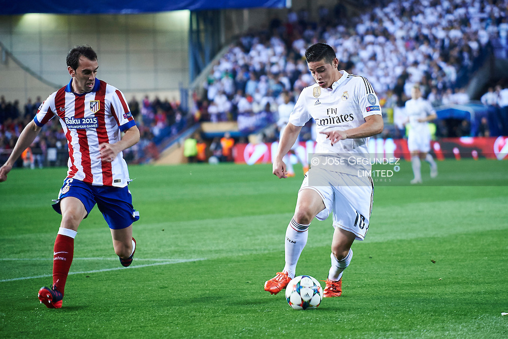 James Rodriguez (Real Madrid F.C.) and Godin in action during the Champions League, round of 4 match between Atletico de Madrid and Real Madrid at Estadio Vicente Calderon on April 14, 2015 in Madrid, Spain