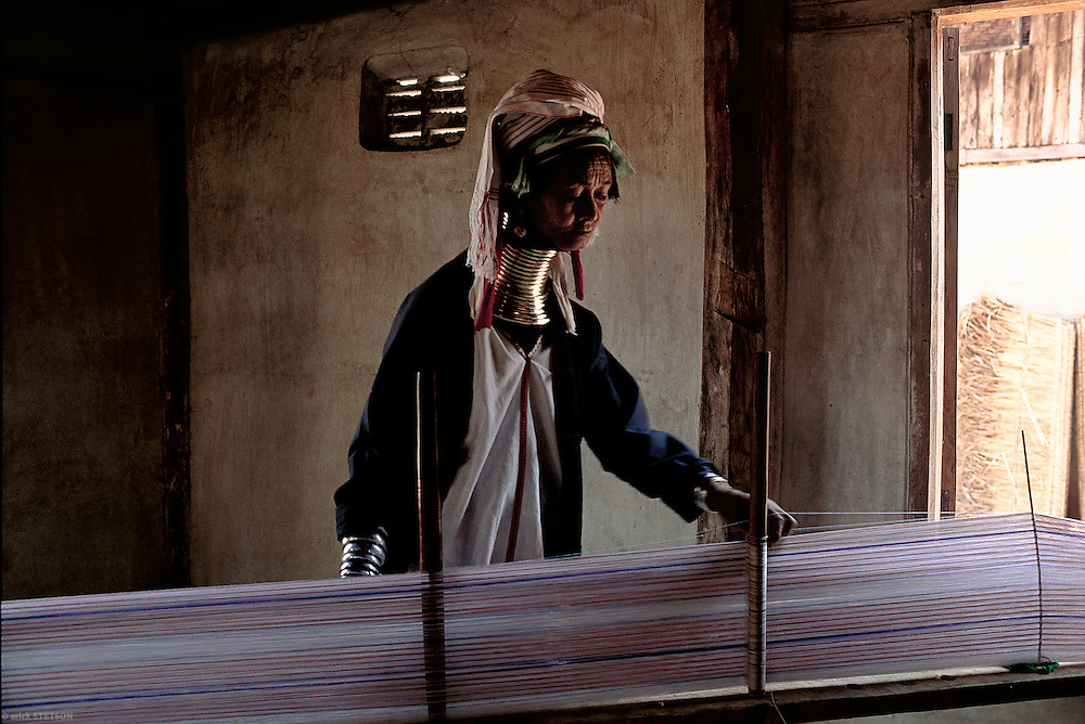 — A Padaung woman, of the Karen people of Burma, weaves a traditional garment on a hand loom.