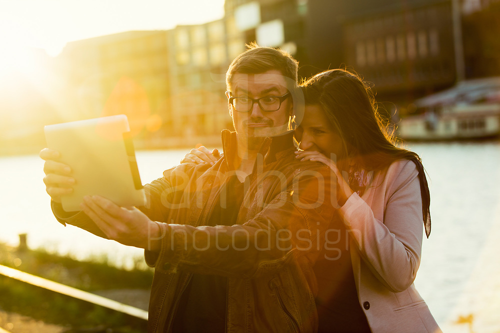 couple on the harbor of münster city late afternoon with tablet