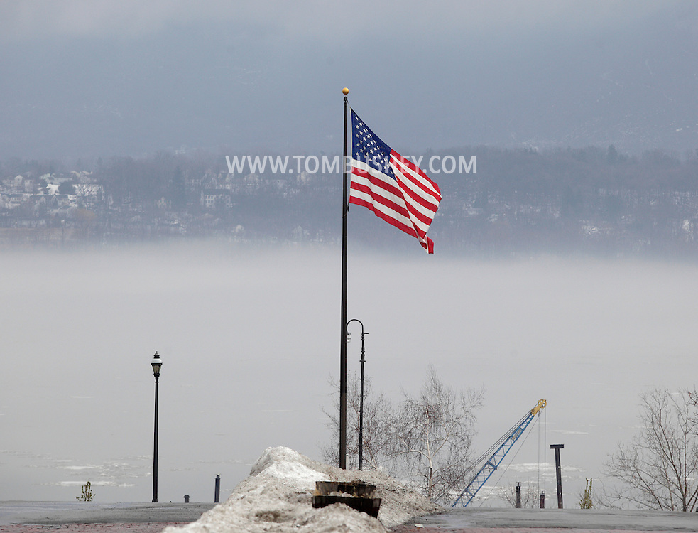 Newburgh, New York - An American flag flies on the Newburgh waterfront above the Hudson River, which is party covered in fog on a warm winter day. Jan. 2, 2010. The City of Beacon is visible on the east side of the river.