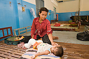 26 JUNE 2006 - SIEM REAP, CAMBODIA: A woman tends to her baby in the woman's dorm at Handicapped International in Siem Reap, Cambodia. Handicapped International helps Cambodians maimed by mines and unexploded ordinance as well as traffic accidents and disease adjust to a life without limbs. Cambodians are still wrestling with the legacy of the war in Vietnam and subsequent civil wars. At one time it was the most heavily mined country in the world and a vast swath of Cambodia, along the Thai-Cambodian border, is still mined. In 2004, more than 800 people were killed by mines and unexploded ordinance still found in the countryside.  Photo by Jack Kurtz / ZUMA Press