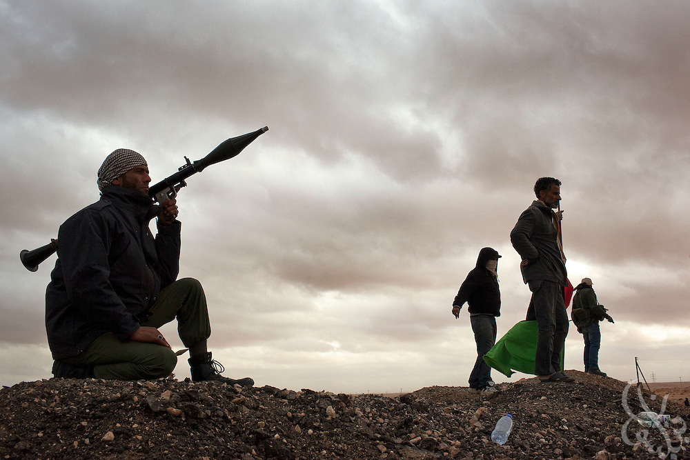 Libyan rebel fighters with RPG and small arms stand watch for pro-Qaddafi jets at a rebel anti-aircraft position position March 08, 2011 in Ras Lanouf, Libya. For more than 2 weeks rebels in Eastern Libya have been battling pro-Qadaffi forces, seeking to topple the nearly 42 year old dictatorship of Col Moammar el-Qadaffi.
