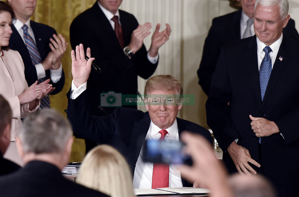 President Donald Trump waves after signing a National Space Directive to establish Space Traffic Management program to address challenge of congestion of satellites and space vehicles in Earth orbit during a meeting with the National Space Council in the East Room of the White House, in Washington, D.C., on June 18, 2018. Photo by Olivier Douliery/ Abaca Press