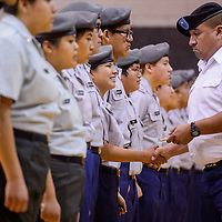 Shelbilynn Pino, center, receives a handshake and a ribbon from Jerry Sanchez during the Army Junior Officer Reserve Training Corps annual awards ceremony at Gallup High School Wednesday.