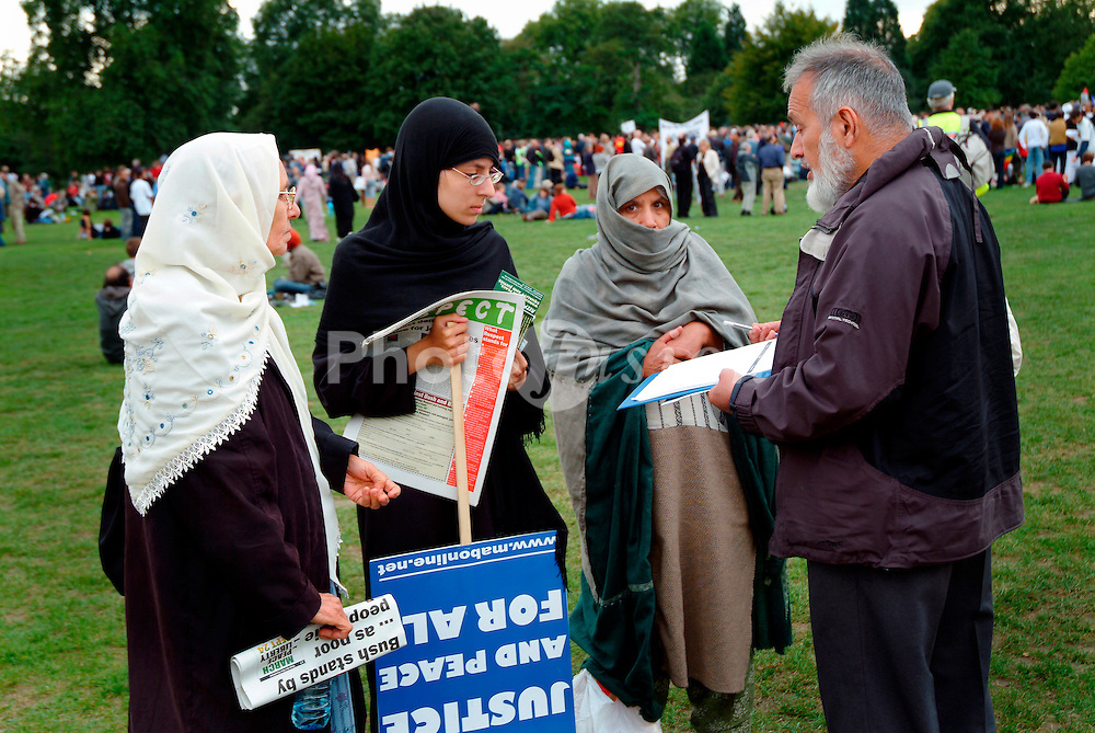 Group of Muslim women talking to a man after rally against war in Iraq; Hyde Park; London Sep 2005 UK