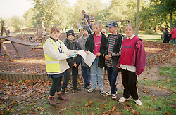 Group of teenagers in park with supervisor preparing to take part in outdoor games,