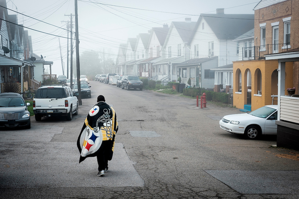 A boy walks along the foggy streets of the McDonald Heights neighborhood of Aliquippa, PA.