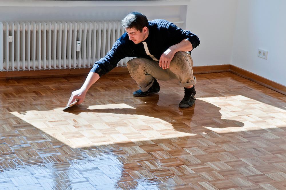 Ein Handwerker trägt verteilt eine Ölschicht zur Versiegelung eines Parkettbodens  |  worker prepares a wooden floor   |