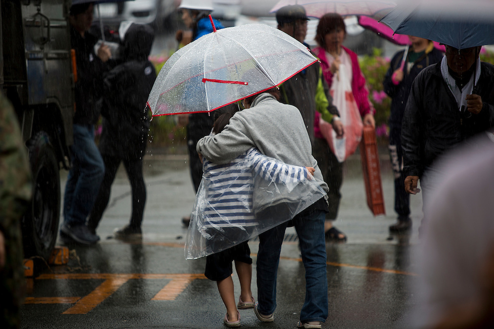 KUMAMOTO, JAPAN - APRIL 21: Earthquake survivor walks in the rain in the morning of April 21, 2016 in Mashiki Gymnasium parking area, Kumamoto, Japan. To date 45 people are confirmed dead and around 11,000 people have evacuated after an 6.5 earthquake on Thursday night and a stronger 7.3 quake on Saturday morning struck the Kyushu Island in western Japan.<br /> <br /> Photo: Richard Atrero de Guzman