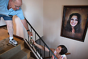 Ralph Paladino passes salad dressing to his wife Rosemarie to give to their granddaughter Marleigh, 17, who is eating dinner in her bedroom, on September 3, 2015. A picture of their daughter, Deanna, who died in 2014 at age 41, hangs on the wall. The Paladinos live primarily on Ralph's police officer's pension and social security, and have home equity loan with an interest rate linked to the prime lending rate. A Fed rate increase would force their already tight budget even further. Photographer: Mike Bradley/Bloomberg
