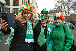 © Licensed to London News Pictures. 17/03/2019. London, UK. Women take a selfie during St Patrick's Day parade in central London. Photo credit: Dinendra Haria/LNP