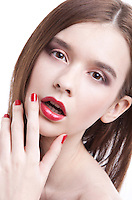 Portrait of beautiful young woman wearing red lipstick with hand on face against white background