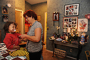 SUN STAR PHOTO BY BEA AHBECK<br /> Renate tries to get a fussy Dessira ready to go to Jasmine's Christmas play, next to the memorial display over her slain daughter in their Atwater house Dec. 16, 2010.