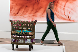 """© Licensed to London News Pictures. 05/06/2018. LONDON, UK. A staff member views """"There's a Lot of Money in Chairs"""", 1994, by Tracey Emin in front of """"Greifbar 1"""", 2014, by Wolfgang Tillmans at a preview of the 250th Summer Exhibition at the Royal Academy of Arts in Piccadilly, which has been co-ordinated by Grayson Perry RA this year.  Running concurrently, is The Great Spectacle, featuring highlights from the past 250 years.  Both shows run 12 June to 19 August 2018.  Photo credit: Stephen Chung/LNP"""