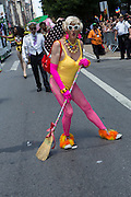 Wearing pink tights and a yelllow bathing suit, a marcher sweeps the street.