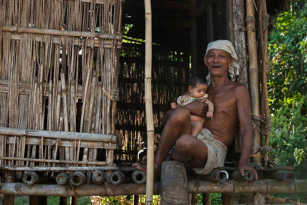 Mising Man at house<br /> Mising Tribe (Mishing or Miri Tribe)<br /> Majuli Island, Brahmaputra River<br /> Largest river island in India<br /> Assam,  ne India